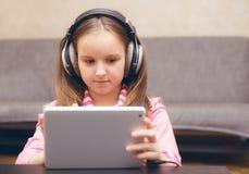 坐在大一张桌和神色上的孩子在计算机 免版税库存图片