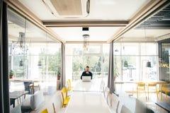 坐在大会议romm白色桌上和工作在膝上型计算机的有胡子的英俊的商人在见面前 图库摄影