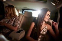 坐在大型高级轿车的两名妇女看在窗口,车视图外面 库存图片