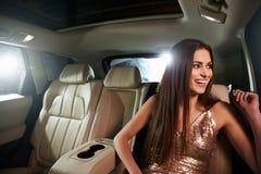 坐在大型高级轿车的深色头发的少妇看在窗口外面 免版税库存图片
