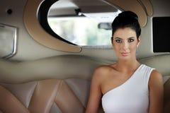 坐在大型高级轿车的美丽的端庄的妇女 免版税库存照片