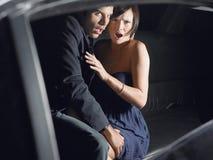 坐在大型高级轿车的震惊夫妇 免版税库存照片