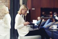 坐在大学图书馆里的女学生,当曾经技术时 免版税图库摄影