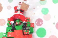坐在大礼物盒和读愿望的圣诞老人 图库摄影