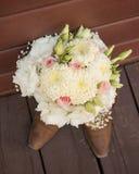 坐在女牛仔起动顶部的新娘花束 库存照片
