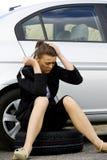 坐在她残破的汽车的沮丧的妇女 免版税库存图片
