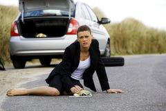 坐在她残破的汽车的沮丧的妇女 库存照片