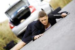 坐在她残破的汽车的沮丧的妇女 免版税图库摄影