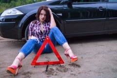 坐在她残破的汽车和警告三角附近的妇女 免版税库存照片