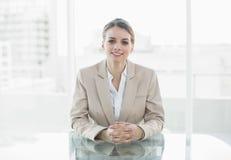 坐在她的书桌的可爱的微笑的女实业家 免版税图库摄影