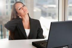 坐在她的书桌的女实业家疲倦 库存照片