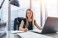 坐在她的书桌的女性首席执行官采取在大事记文字的笔记与笔和使用她的计算机在现代 库存图片