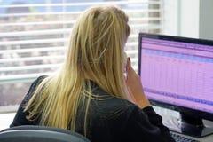 坐在她的书桌的妇女运转和回答电话 库存照片