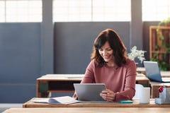 坐在她的书桌的年轻女实业家使用一种数字式片剂 库存图片