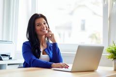 坐在她的书桌的愉快的妇女与笔记本一起使用 免版税库存图片