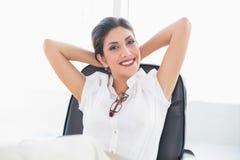 坐在她的书桌的斜倚的女实业家微笑对照相机 免版税库存图片