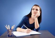 坐在她的书桌的年轻沉思学生 免版税库存图片