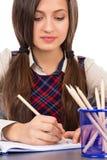 坐在她的书桌被集中和做h的学生特写镜头 免版税库存照片