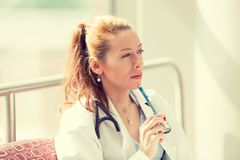 坐在她的办公室的一位确信的妇女医生的画象 免版税库存图片