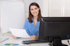 坐在她的办公室的成功的年轻微笑的女商人 免版税库存图片