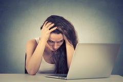 坐在她的在计算机前面的书桌的困被注重的少妇 免版税库存照片