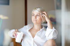 坐在她的屋子里的严肃的年轻白肤金发的妇女沉思地看在开窗口 美好的早晨光点燃了 免版税库存图片