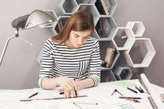 坐在她的工作场所的严肃的年轻悦目女性建筑师画象,做与铅笔和统治者的图画 图库摄影