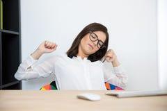 坐在她的工作场所的女实业家 库存图片