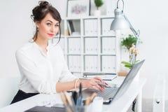 坐在她的工作场所的年轻女实业家,制定出新的企业想法,佩带的正式衣服和玻璃,看 免版税库存照片