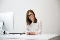 坐在她的工作场所的愉快的女实业家在办公室 库存图片