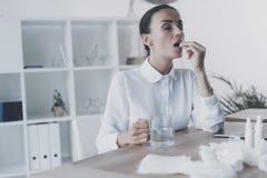 坐在她的工作场所的病的妇女在办公室 她在她的手上拿着一个药片 免版税库存照片