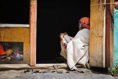 坐在她的房子前面的印地安妇女 库存照片