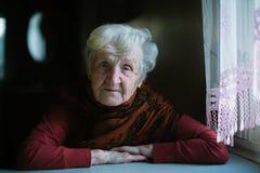 坐在她的房子里的一把黑暗的钥匙的年长妇女在窗口附近 免版税库存照片