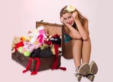 坐在她的手提箱附近的妇女的新针 库存图片