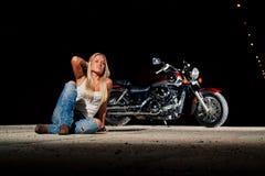 坐在她的摩托车附近的性感的金发碧眼的女人 免版税库存图片
