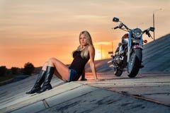 坐在她的摩托车附近的年轻性感的金发碧眼的女人 免版税库存照片