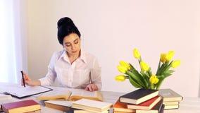坐在她的有书的书桌的许多工作疲乏的困年轻女人 股票视频