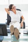 坐在她的有她的微笑对照相机的脚的书桌的轻松的女实业家 免版税库存照片