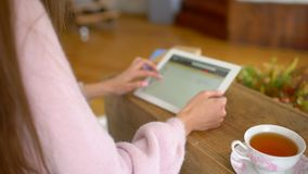 坐在她的有片剂计算机的书桌的妇女看网上零售服装店网站 站点显示各种各样 股票录像