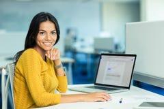坐在她的有膝上型计算机的工作场所的女实业家 图库摄影