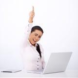 坐在她的服务台的愉快的妇女,当一条胳膊rised 免版税库存照片