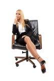 坐在她的椅子的女实业家 免版税图库摄影