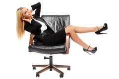 坐在她的椅子的女实业家 免版税库存图片
