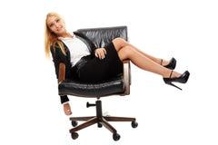 坐在她的椅子的女实业家 图库摄影