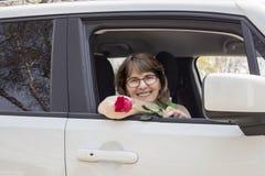坐在她的汽车的年轻妈妈拿着一朵红色玫瑰 库存图片