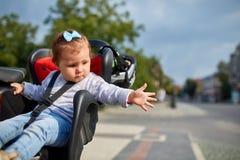 坐在她的父亲安全情感忧虑自行车的婴孩自行车位子的女孩哄骗儿童做父母 库存图片