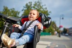 坐在她的父亲安全情感忧虑自行车的婴孩自行车位子的女孩哄骗儿童做父母 免版税库存图片