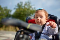 坐在她的父亲安全情感忧虑自行车的婴孩自行车位子的女孩哄骗儿童做父母 免版税库存照片