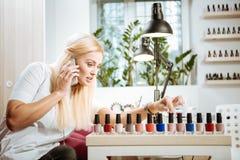 坐在她的美容院的兴旺的女性企业家 免版税图库摄影