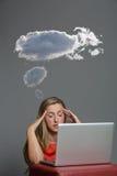 坐在她的膝上型计算机前面的白肤金发的妇女 库存照片